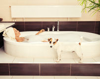 Dog beside the woman in the bathroom Royalty Free Stock Image