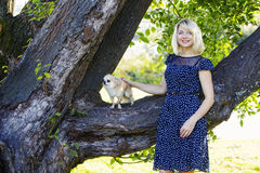 Dog and woman posing in summer park. Lady in blue polka-dot dress with dog Royalty Free Stock Photography