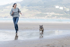 Dog and woman running and playing in the beach. Royalty Free Stock Images