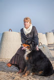 Dog and woman sitting near sea Stock Image
