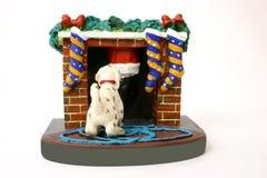 Dog Yanks Santa's Leg. Dog greets santa at the fireplace stock photo