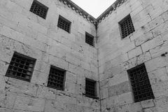 Doge Palace Prison. Ominous view up the walls of the prison of the Doge Palace in Venice, showing the barred windows royalty free stock photography