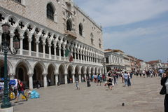 Doge's Palace and promenade. Venice, Italy: Doge's Palace, in the famous central St.Mark square, Architectural detail and people walking on the promenade Stock Images
