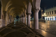 Doges Palace arcade at night. Doges Palace arcade with S.Theodor column and Biblioteca Marciana view in winter night Royalty Free Stock Photo