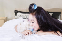 Doggie of Maltese licked a woman. Doggie of Maltese is licking the face of young female while lying in the bedroom Stock Images