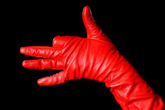 Doggy. Hand in red glove on the black background showing a dog Royalty Free Stock Photo