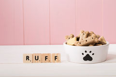 Doggy bowl for filled with biscuits. Doggy bowl decorated with a paw print filled with dried dog biscuits against a wooden pink background with copyspace Stock Photos