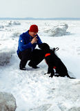Doggy Training. Man and his dog take a moment to review some basic commands while out walking on the ice flows of Georgian Bay, Ontario Stock Photos