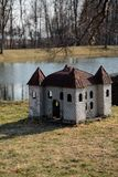 Doghouse in shape of a castle on the river bank in a park stock photography
