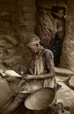 Dogon village, Dogon land, Tireli, Mali, Africa. Tireli, Mali, Africa - January 30, 1992: Dogon village and typical mud buildings, old woman works the wool with Royalty Free Stock Photography