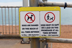 Dogs and the beach sign. Sign explaining when dogs are banned or kept on a lead Stock Photography