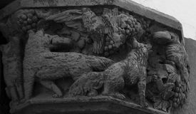 Dogs on fight with some birds. Shot in black and white, detail on the sculpture on the capital on the facade of this historic building representing some animals Royalty Free Stock Images
