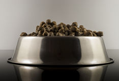 Dogs food. Brown dogs food in bowl on black background royalty free stock image