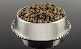 Dogs food. Brown dogs food in bowl on black background stock photography