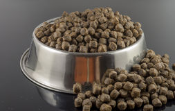 Dogs food. Brown dogs food in bowl on black background stock photos