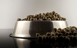 Dogs food. Brown dogs food in bowl on black background royalty free stock images