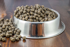 Dogs food. Brown dogs food in bowl on wood table royalty free stock photography