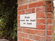 A dogs must be kept of lead white and black simple sign nailed t. O a brick wall on the outside near a carpark and park no people Stock Image