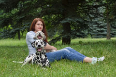 Dogs and their owner sitting on the grass stock photos