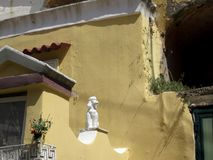 Dogville :以淡色黄色绘的房子,与雕塑  库存照片