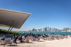 Doha, Κατάρ - 8 Ιανουαρίου 2018 - ντόπιοι και τουρίστες που απολαμβάνουν έναν φραγμό καφέδων με τον ορίζοντα Doha ` s στο υπόβαθρ στοκ εικόνα