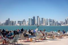 Doha, Κατάρ - 8 Ιανουαρίου 2018 - ντόπιοι και τουρίστες που απολαμβάνουν έναν φραγμό καφέδων με τον ορίζοντα Doha ` s στο υπόβαθρ στοκ φωτογραφία