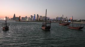 Doha Bay seafront. Scenary seafront landscape of Doha Bay at sunset. Traditional dhows and West bay skyline at evening. Urban cityscape of Doha, Qatari capital stock video footage