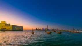 Doha Bay seafront. Time lapse: seafront landscape of Doha Bay after sunset. Traditional dhows and West bay skyline at evening. Urban cityscape of Doha, Qatari stock video footage