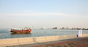 Doha Corniche locals and boat Stock Photo