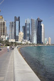 Doha Corniche (Qatar). The Corniche - a pedestrian zone along the bay - with skyscrapers of the city center in Doha, the capital of Qatar Stock Photos