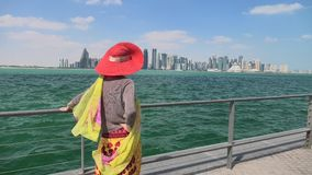 Doha Corniche Woman. Carefree woman with wide hat enjoys the seascape of Corniche promenade of Doha Bay in Qatar. Lifestyle caucasian tourist looking at the tall stock video footage