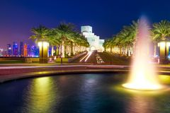 Doha Fountain by night. Fountain water reflecting near Corniche with skyscrapers of West Bay skyline illuminated on background. Doha, Qatari capital, in Middle stock images