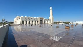 Doha Grand Mosque. Scenic Doha Grand Mosque with a minaret at sun light reflecting on the outdoor pavement. Qatar State Mosque, Middle East, Arabian Peninsula in stock footage