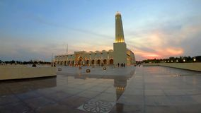 Doha Grand Mosque. Scenic Doha Grand Mosque with a minaret at sunset light reflecting on the outdoor pavement. Qatar State Mosque, Middle East, Arabian Peninsula stock footage