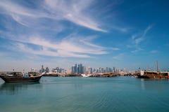 DOHA KATAR, Feb, - 2018: Piękny Doha linii horyzontu widok z Tradycyjnymi Drewnianymi łodziami z Unosić się Katarskie flaga Corni obrazy stock