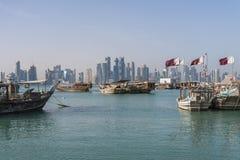 DOHA, KATAR - Februar 2018: Schöne Doha-Skyline-Ansicht mit traditionellen hölzernen Booten mit dem Schwimmen von Katar-Flaggen C lizenzfreie stockbilder
