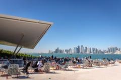 Doha, Katar - 8. Januar 2018 - Einheimische und Touristen, die eine Caféstange mit Doha-` s Skylinen im Hintergrund an einem Tag  stockbild