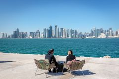 Doha, Katar - 8. Januar 2018 - Einheimische und Touristen, die eine Caféstange mit Doha-` s Skylinen im Hintergrund an einem Tag  stockfotografie
