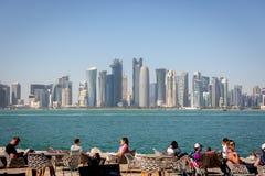 Doha, Katar - 8. Januar 2018 - Einheimische und Touristen, die eine Caféstange mit Doha-` s Skylinen im Hintergrund an einem Tag  lizenzfreie stockfotografie