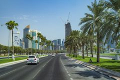 DOHA, KATAR - 4 2018 SIERPIEŃ: Nowożytny miasto Doha z drzewkiem palmowym, samochody, szerokie aleje na niebieskim niebie w Doha  obraz royalty free