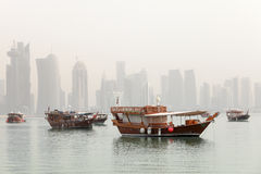 Doha in the mist. Dhows in Doha Bay, Qatar, June 2012, with the Arab capital's 21st Century skyline still under construction in the background, partly obscured Stock Images
