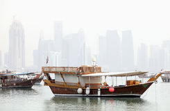 Doha in the mist. Dhows in Doha Bay, Qatar, June 2012, with the Arab capital's 21st Century skyline still under construction in the background, partly obscured Royalty Free Stock Photography
