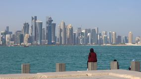 Doha Modern City Skyline Day Shot, Qatar, Middle East. Arabian Woman in a Cape Sitting on Concrete Brick and Looking at. Doha City Downtown from Corniche stock video
