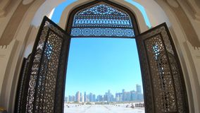 Doha Mosque entrance. Modern skyscrapers of Doha West Bay skyline view from State Grand Mosque in Doha, Qatar, Middle East, Arabian Peninsula. Door of entrance stock footage
