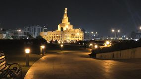 Doha Mosque at night. Bench and walkway in Souq Waqif Garden near Doha Corniche with Doha mosque on background. Doha center in Qatar, Middle East, Arabian stock video