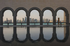 Doha Museum of Islamic Art. The Doha skyline in late afternoon sun captured through the arches behind the museum of Islamic art in Doha Royalty Free Stock Images