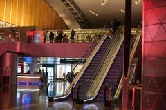DOHA, QATAR - 28 DE ABRIL DE 2018: Escalera móvil de Hamad International Airport y mostrador de información para el pasajero colo imágenes de archivo libres de regalías
