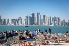 Doha, Qatar - 8 de enero de 2018 - Locals y turistas que gozan de una barra del café con horizonte del ` s de Doha en el fondo en fotos de archivo