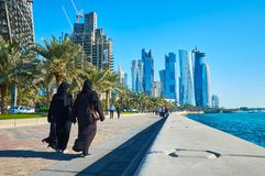 The popular walking streets of Doha, Qatar. DOHA, QATAR - FEBRUARY 13, 2018: The Corniche promenade is popular seaside area, tourists and locals enjoy the walks Stock Photos