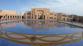 Katara Village reflections. Doha, Qatar - February 17, 2019: Katara cultural village reflecting in a tiled pool with fountain in West Bay District, Qatar. Middle stock video footage